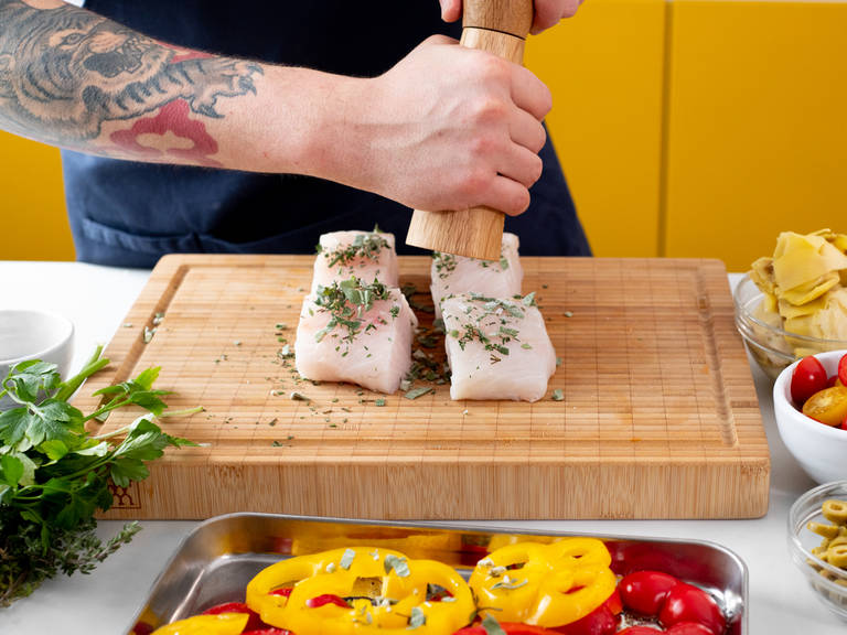 Kabeljaufilets mit einem Teil des gehackten Salbei und Thymian sowie Salz und Pfeffer würzen und beiseitestellen. Paprika auf ein mit Backpapier ausgelegtes Backblech legen und mit Olivenöl beträufeln. Mit den restlichen Kräutern, Salz und Pfeffer würzen. Im Ofen für ca. 15 Min. backen.
