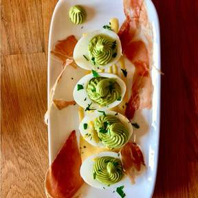 Deviled eggs with avocado cream and prosciutto